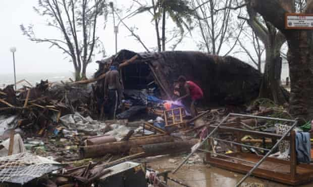 In this image provided by UNICEF Pacific people scour through debris damaged and flung around in Port Vila, Vanuatu, Saturday, March 14, 2015, in the aftermath of Cyclone Pam. Winds from the extremely powerful cyclone that blew through the Pacific's Vanuatu archipelago are beginning to subside, revealing widespread destruction. (AP Photo/UNICEF Pacific, Humans of Vanuatu) EDITORIAL USE ONLY, NO SALES