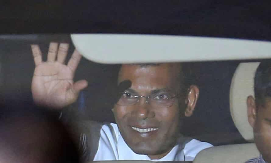 Mohamed Nasheed waves to reporters from inside a car outside the court after a three-judge panel pronounced his verdict.