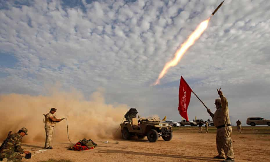 Shia fighters launch a rocket during clashes with Isis militants on the outskirts of al-Alam on 8 March. Photograph: Thaier Al-Sudani/Reuters