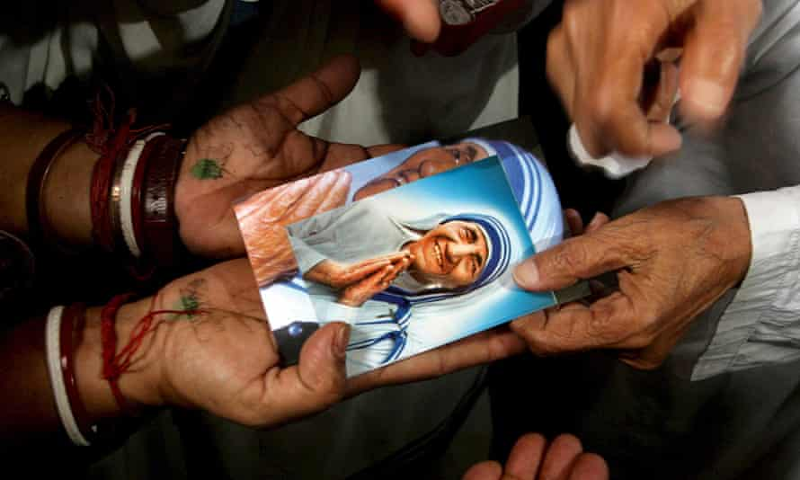 Photos of Mother Teresa are distributed in Kolkata  during a mass prayer session on the 98th anniversary in 2008 of her birth