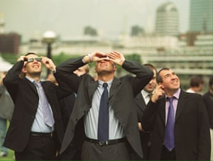 City workers take time out to view the eclipe in London