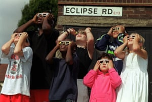 Children watch the sky from Eclipse Road in East London