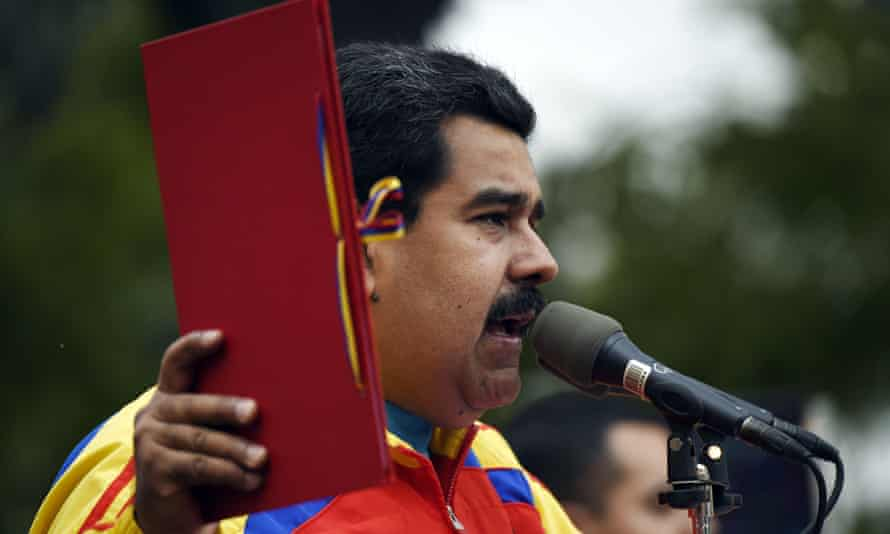 Nicolas Maduro holding the folder with the decree powers law in Caracas on Sunday.