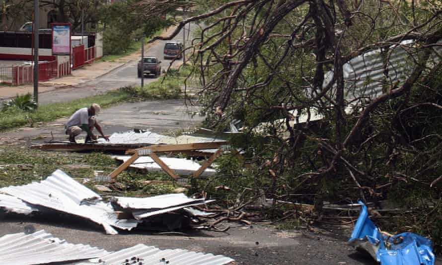 A local resident kneels near debris on a street near damaged homes in Port Vila.