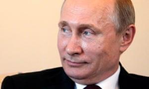 Putin listens to Atambayev during their meeting.