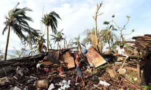 A young boy plays with a ball as his mother searches through the ruins of their family home on March 16, 2015 in Port Vila, Vanuatu. Cyclone Pam has hit South Pacific islands on Saturday with hurricane force winds, huge ocean swells and flash flooding and has caused severe damage to housing. Aid agencies say it could be one of the worst disasters ever to hit the region.