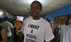 Adesina Afeez Adebare displays his voter's card at an Inec centre.