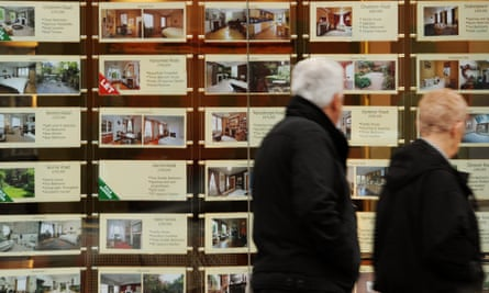 Older couple walking past an estate agents window