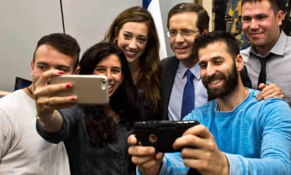 Yitzhak Herzog (third from right) poses for selfie photographs with supporters on Monday.