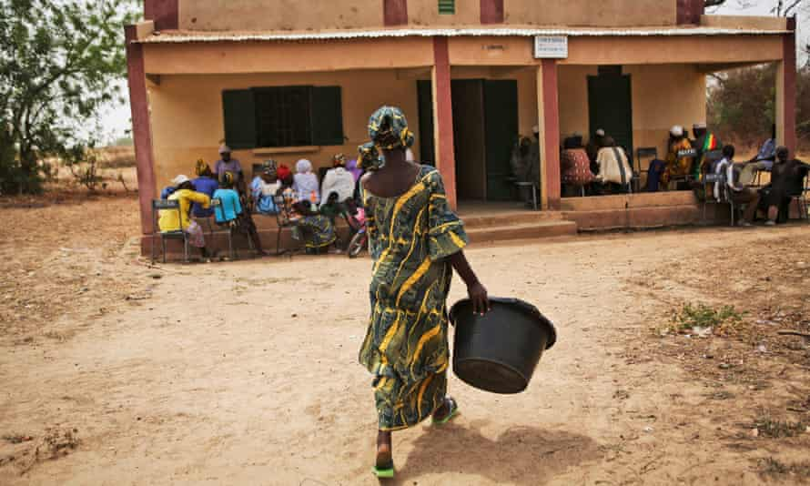 Nurse Vinima Baya, 29, retrieves a big tub that women in labour use to bring clean water to the clinic when they are giving birth, at the community health centre (pictured) in the village of Diatoula, 15km outside of Bamako, Mali.