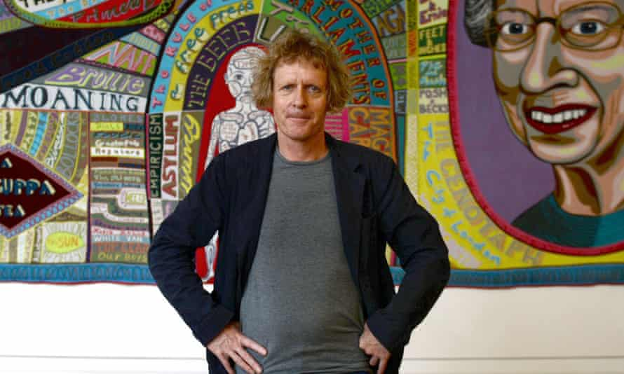 Grayson Perry in front of his tapestry Comfort Blanket at the National Portrait Gallery in London
