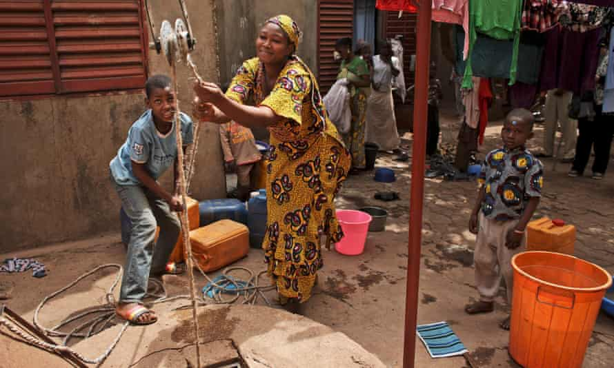 Sally Cisse, right and neighbour Mamadou Coulibaly, pull up unclean water from a well in the courtyard of 16-year old Adiaratou Togo's house, where she lives with her 3-day old baby boy, near the South extension community health centre, in Kalabancoro, a town on the outskirts of Bamako, Mali. (WaterAid/Tara Todras-Whitehill)