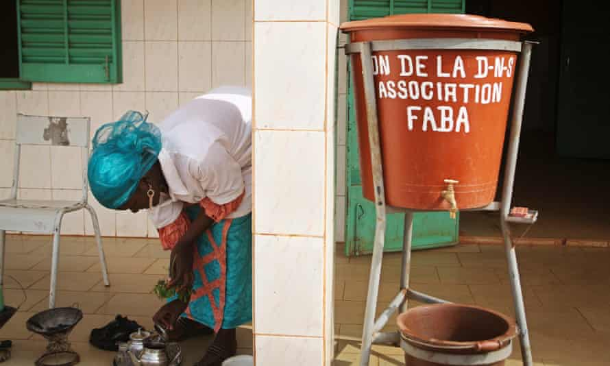 Nenekoulu Bady, 21, an obstetrical assistant at the community health centre, makes tea outside the clinic in Kalabancoro.