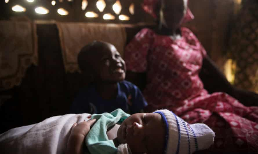 Sountou Sissoko, 22, right, looks on as her eldest son Daouda, three, plays with his newborn brother Alaye, seven days old, at the family house near the South extension community health centre where she gave birth, in Kalabancoro, Mali. (WaterAid/Tara Todras-Whitehill)