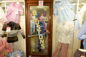 Shutting up shop: Michael Albert closes the door of Blustons clothes.