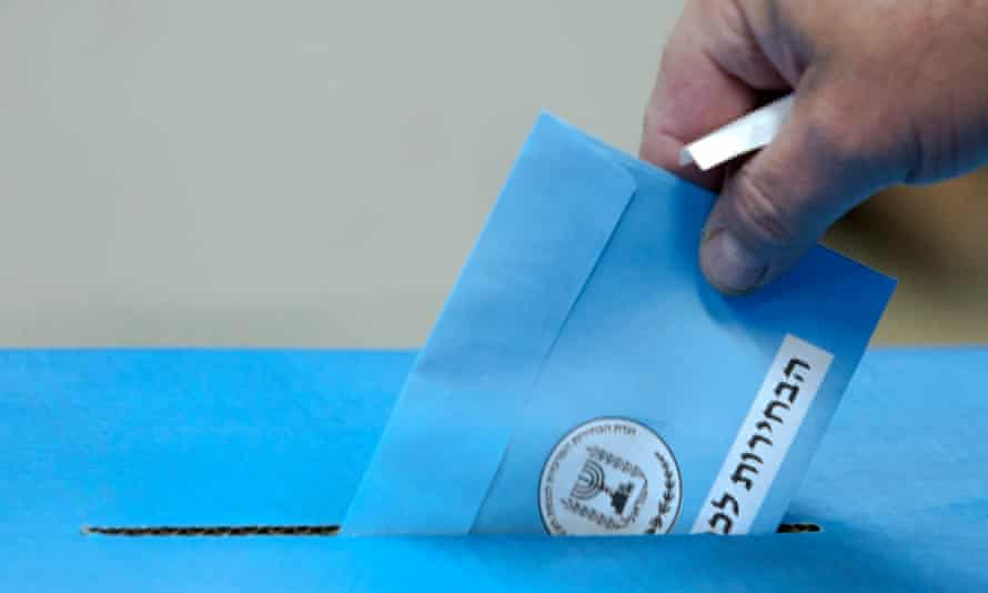 An Israeli drops his ballot into the ballot box as he votes in the general election in Tel Aviv.