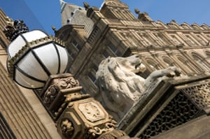 A carved lion and ornate lamp outside Leeds Town Hall.