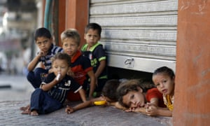 Displaced Palestinian children peak from under a shop door, where their family is taking shelter in Gaza City in July 2014.