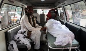 body in white sheet lies in ambulance