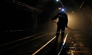 A miner walks along tracks used for transporting coal in Xiaoyi, Shanxi province, China.