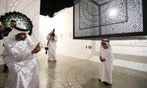 The crown Prince of Dubai, Sheikh Hamdan bin Mohammed bin Rashid al-Maktoum (L), snaps a picture at Art Dubai 2015.