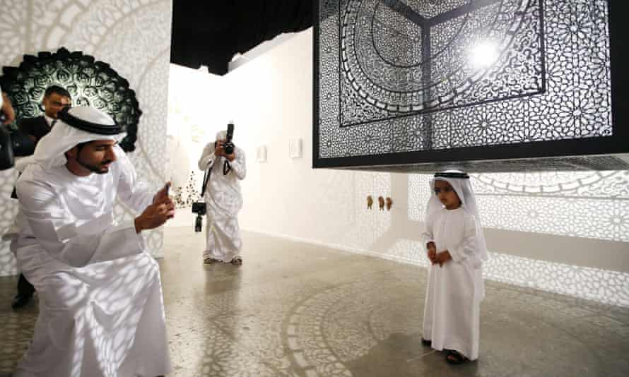 The crown Prince of Dubai, Sheikh Hamdan bin Mohammed bin Rashid al-Maktoum (L), snaps a picture at Art Dubai 2015.