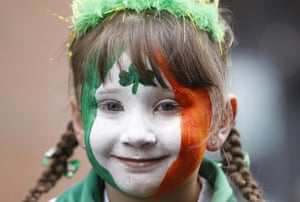 A girl participates in St Patrick's day celebrations as she waits for a parade in the centre of Belfast, Northern Ireland