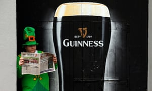 A man dressed as a leprechaun reads a newspaper  in the city of Londonderry, Northern Ireland