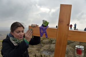 A woman touches the cross as hundreds of people make the St. Patrick's Day pilgrimage to the top of Slemish mountain in Ballymena, Northern Ireland