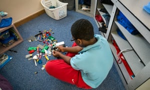 One of the children at Clayfields House plays with Lego in his room.