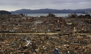A Japanese survivor of the magnitude 9.0 earthquake rides his bicycle through the leveled city of Minamisanriku in 2011. Debris from the natural disaster continues to wash onto the US west coast.