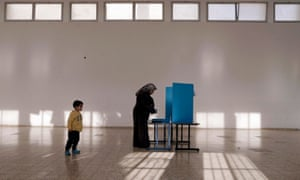 An Israeli Arab stands behind a voting booth before casting. With results so tight, the new government in Israel could take many forms.