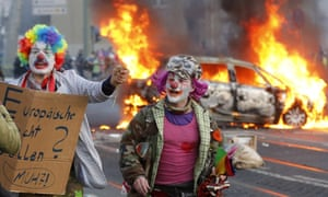 Demonstrators dressed as clowns pass by a burning police car during the Frankfurt protests.