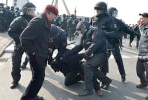 Several policemen overpower a demonstrator