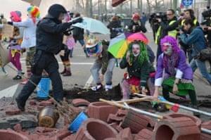 Dressed up demonstrators climb over a blockade