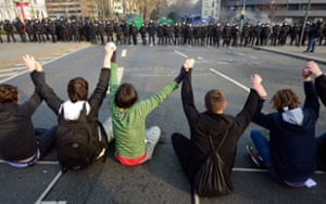 Activists sit and hold hands in front of a police cordon
