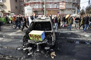 A burnt car with a protest message as protesters walk by