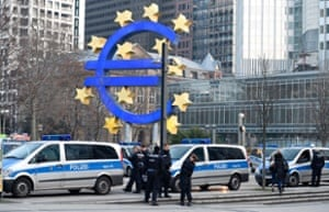 Police stand in front of the logo of the Euro at the European Central Bank