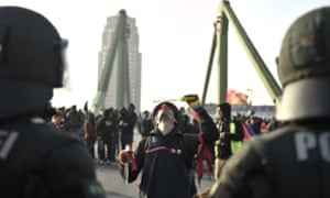 An activist with a clown nose in front of riot police