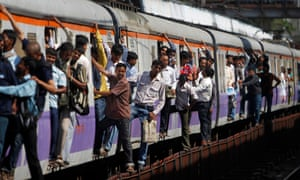 Commuters hang on the outside of a local train in Mumbai. According to some estimates, more than 5,000 people can cram into carriages designed to carry no more than 1,700.