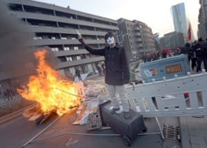 A demonstrant protests in front of a burning barricade
