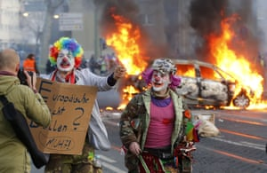 Demonstrators dressed as clowns pass by a burning police car