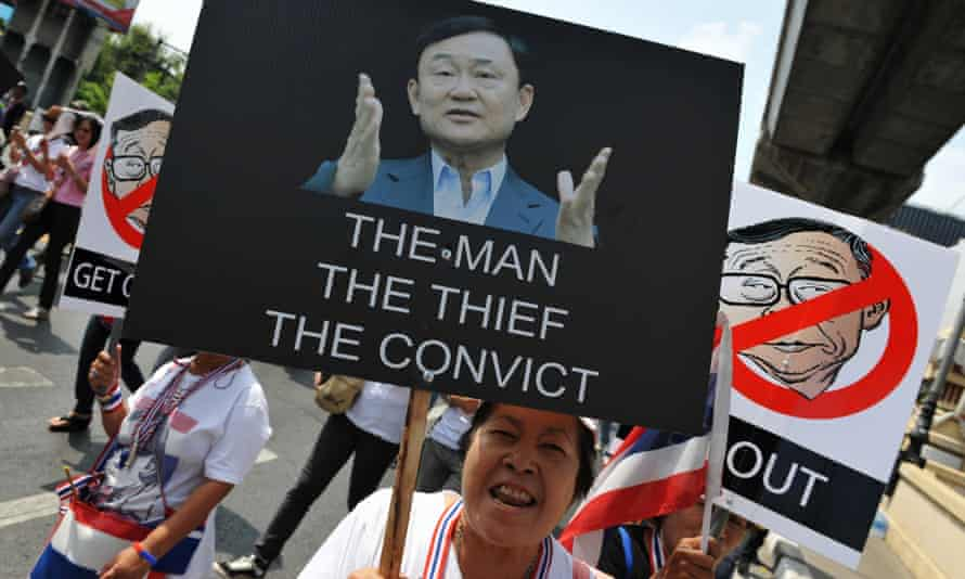 Sign of the times: an anti-government protester holds up a placard depicting former self-exhiled Thai prime minister Thaksin Shinawatra during a march through Bangkok.