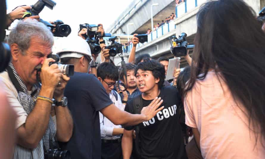An anti-coup activist fights off being restrained during a demonstration in central Bangkok on Valentines Day after handing out roses and copies of George Orwell's Nineteen Eighty-four.