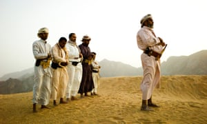 A tribal sheikh and his men praying in the dunes of Marib province