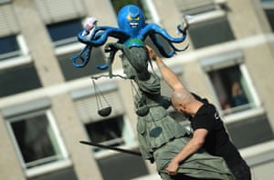 A protester places an octopus figure, holding euro banknotes in its tentacles, on the statue of Justitia