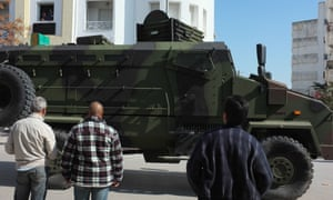A big green and black tank drives through the streets of Tunis as local people watch