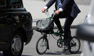 A city gent rides a folding cycle among traffic in central London.