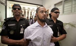 Members of Bangladesh's Rapid Action Battalion force escort Farabi Shafiur Rahman.