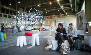 Visitors sit on a couch in a former hangar during the DMY International Design Festival in June 2013.